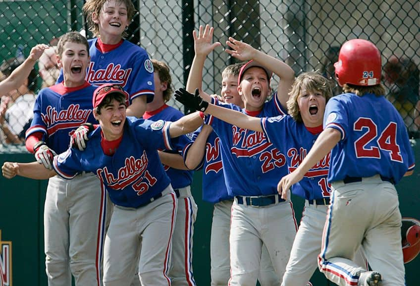 boys little league super happy and high fiving