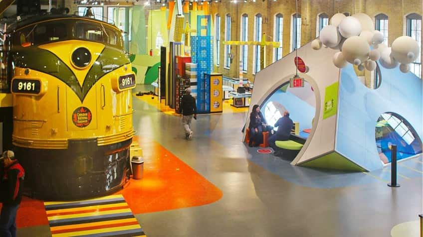 A colourful room with a big blue tent to play in and an actual giant yellow train