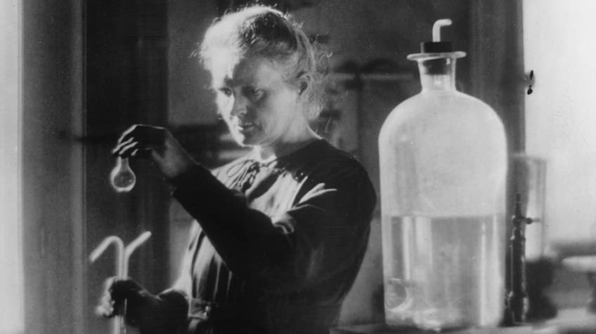 Marie Curie holding a test tube in her lab.