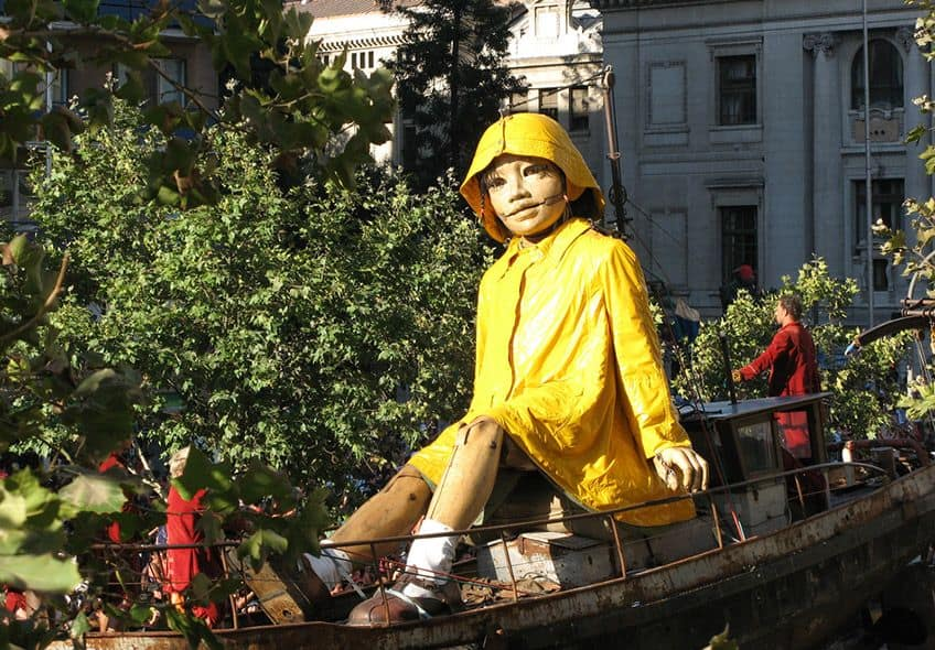 a giant marionette sitting in a boat