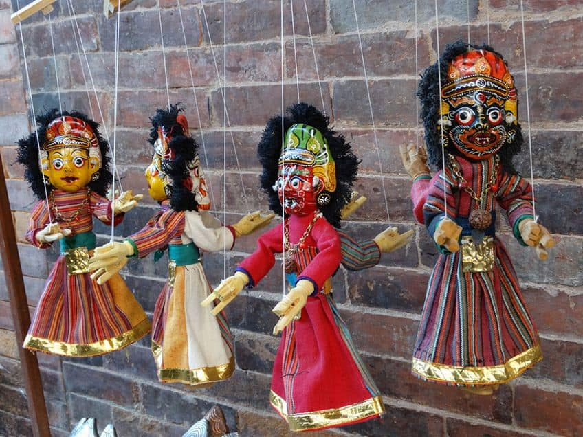 marionettes in colourful costumes and painted masks hanging on a wall