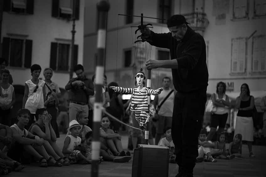 a street performer works his marionette in front of a group of people