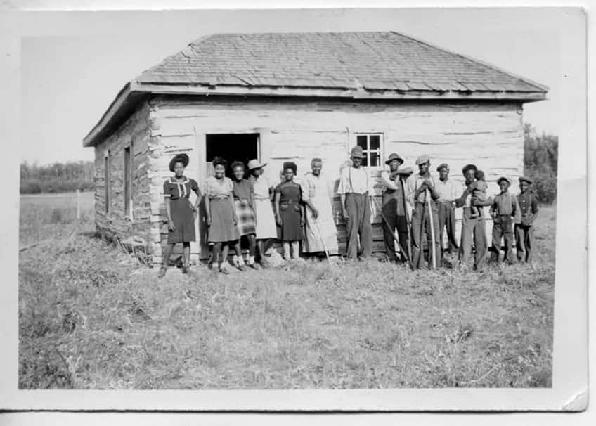 three generations of the Mayes family stand in front of the small church that Joe built