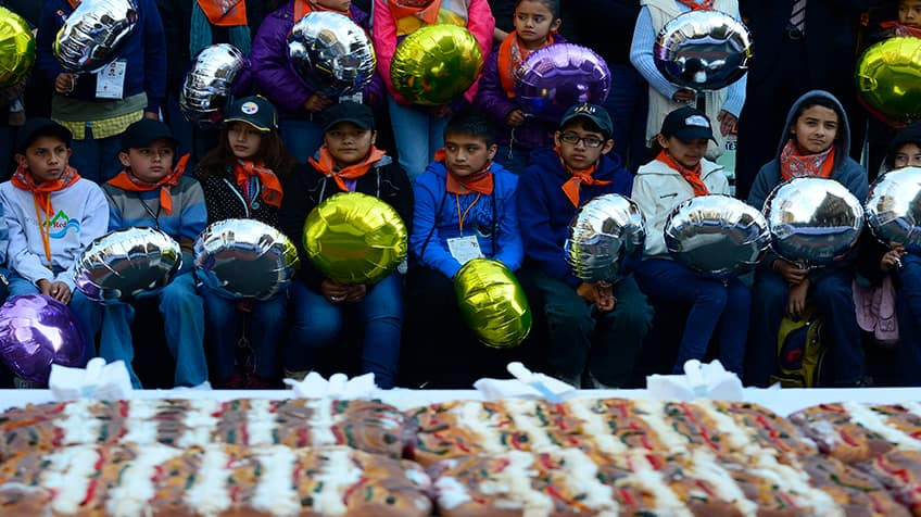 Mexican kids wait for a piece of 'Rosca de Reyes' Epiphany bread.