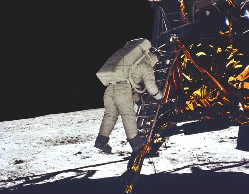historical image of Buzz Aldrin descending from the moon lander to take his first step on the surface of the moon