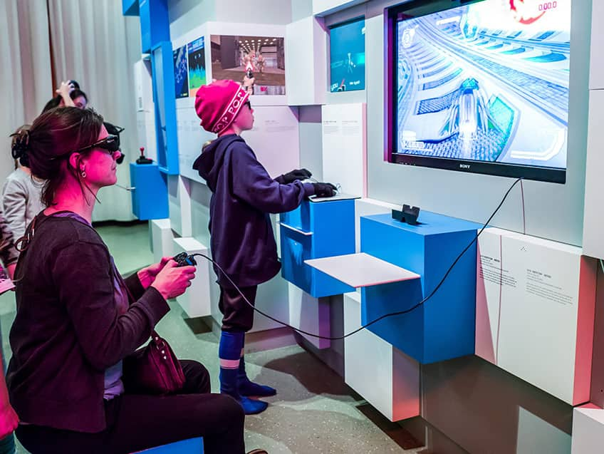 a mom and child playing a 3D video game