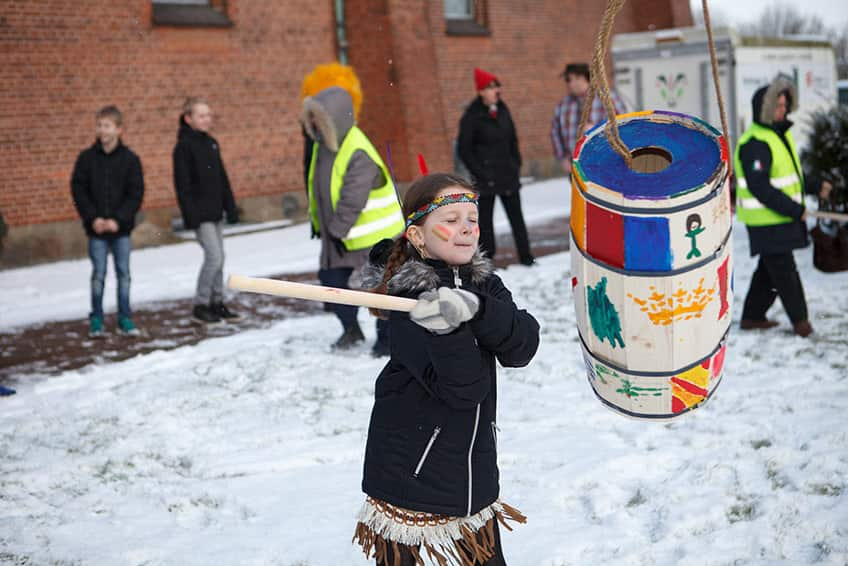 A young girl hits a wooden barrel with a stick to try and get the candy out