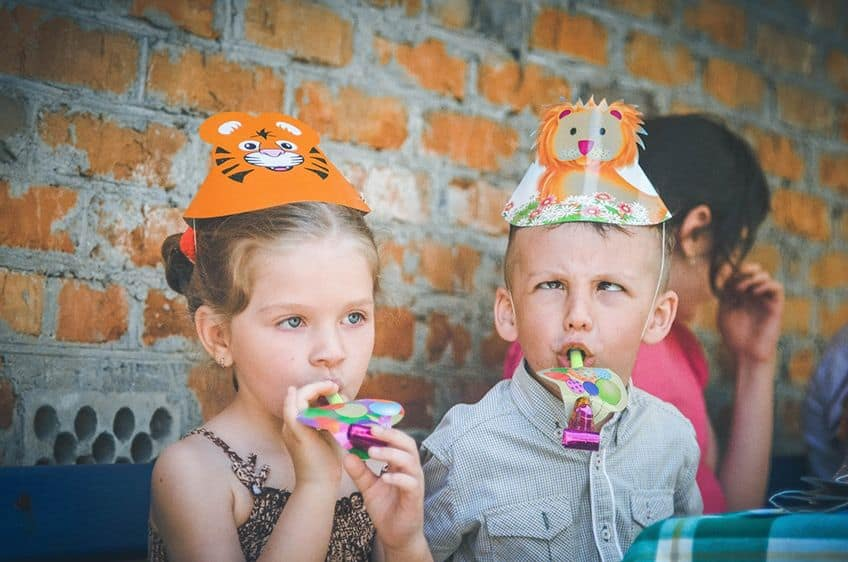 a young girl and boy in party hats and the boy is acting goofy