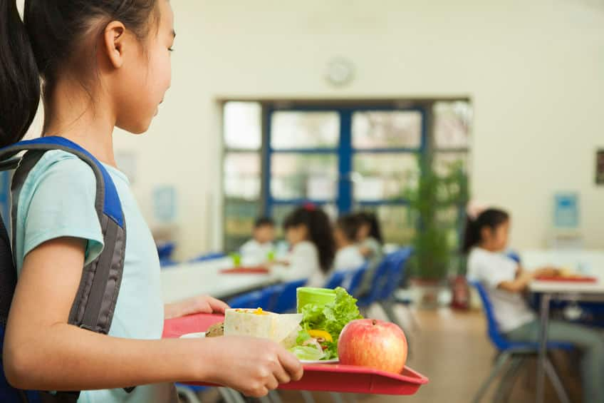 a young girl in a cafeteria holding a tray of food