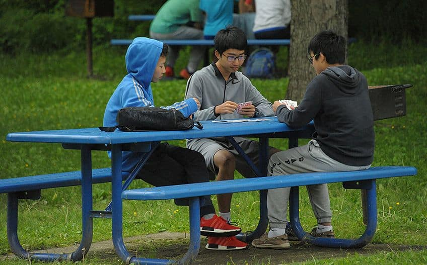 three boys sitting at a picnic table playing cards