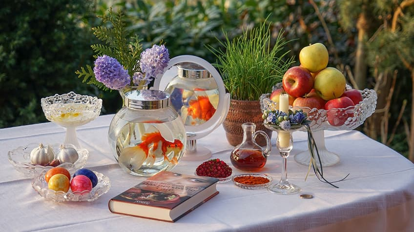 Haft-sin table for Nowruz includes flowers, goldfish, garlic, painted eggs, apples, candles and greenery.
