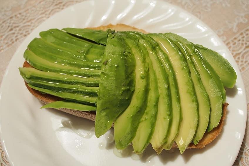 тост с мягкими ломтиками авокадо, посыпанный солью и перцем