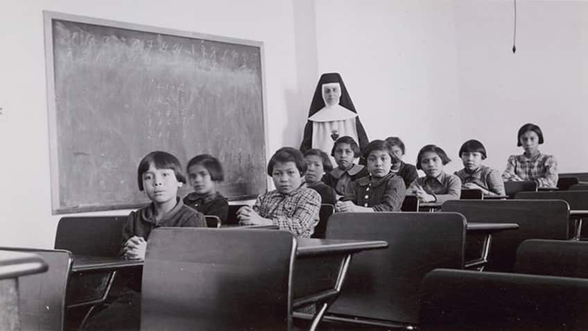 archival black and white photo of a residential school classroom with students and a nun