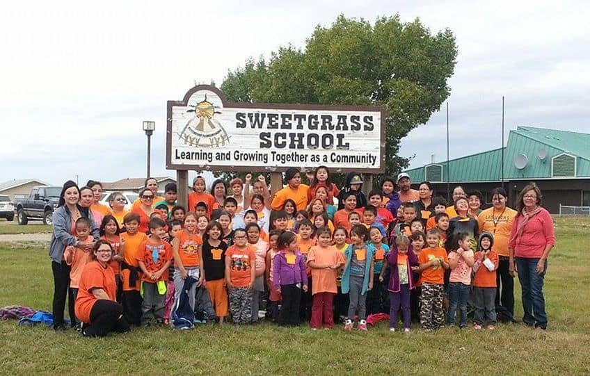 a classroom of children all wearing orange shirts and standing outside in front of their school sign