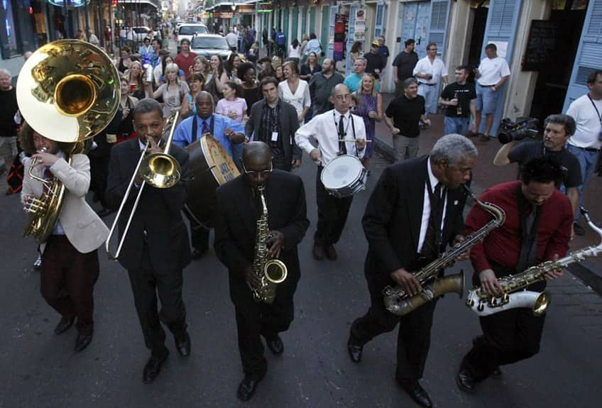 A jazz band plays while walking down a street in New Orleans, followed by a huge crowd of music lovers