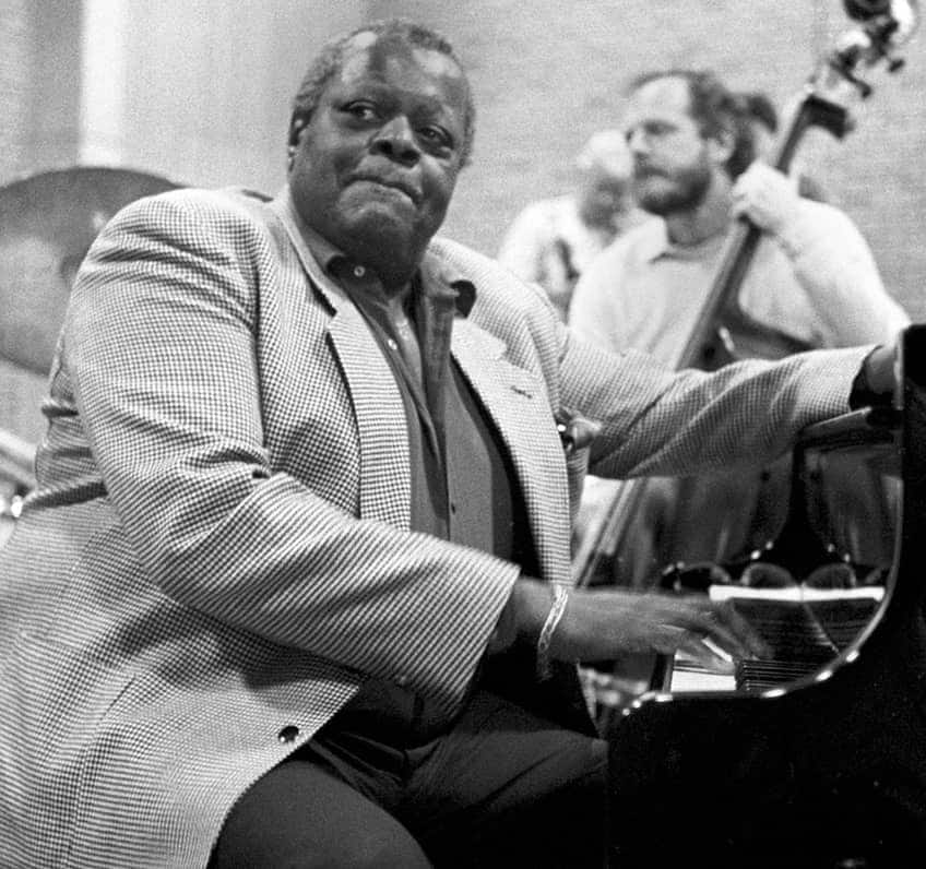 An older Oscar Peterson sits in his favourite place, at the piano surrounded by a band of musicians
