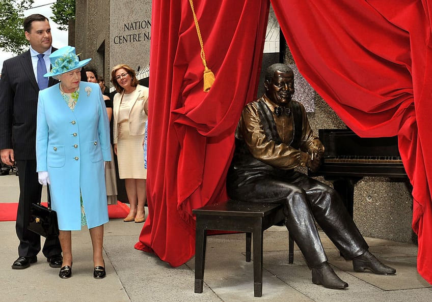 Queen Elizabeth II look on as the statue of Oscar Peterson sitting at his piano is unveiled