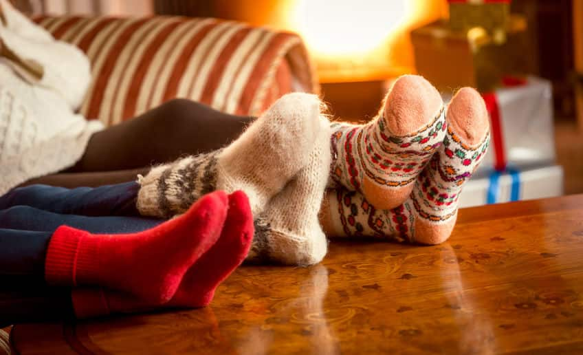 Three people's feet up on the coffee table wearing very warm sock