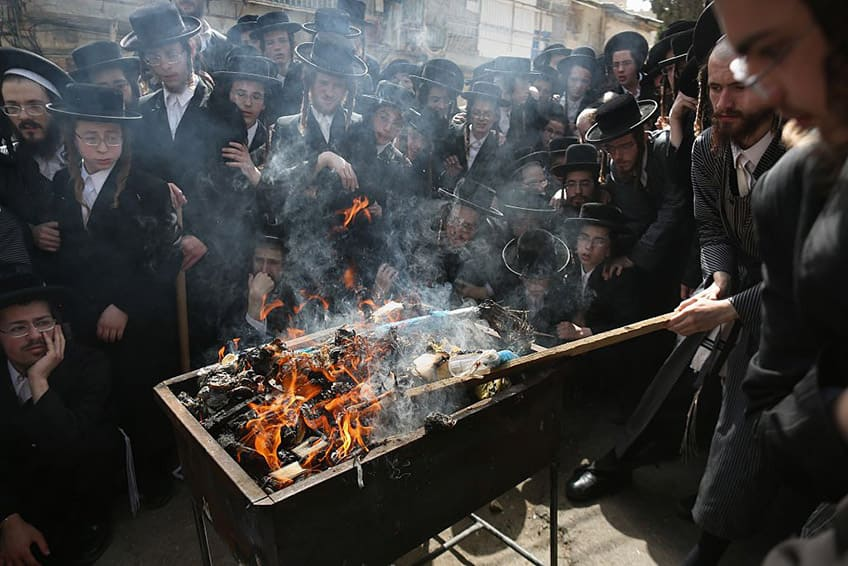 a group of Ultra-Orthodox Jewish men burn leavened food before Passover