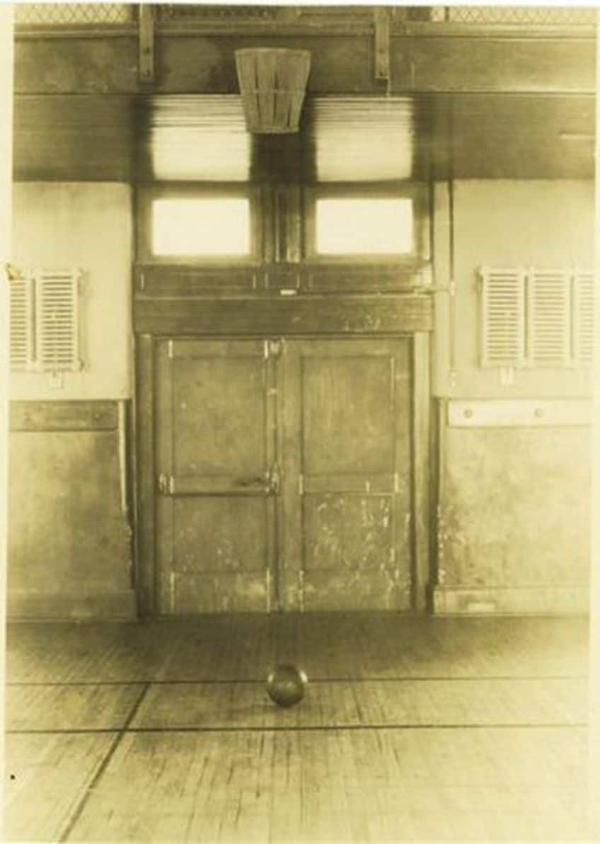 A historic basketball court, complete with a peach basket for the net.
