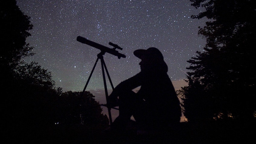 silhouette of a stargazer against the night sky