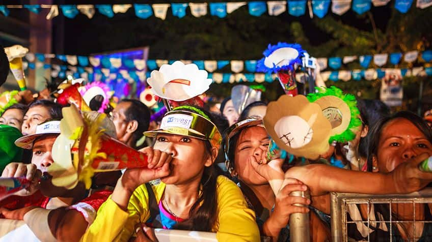New years revellers blow on their noise makers in the Phillippines.