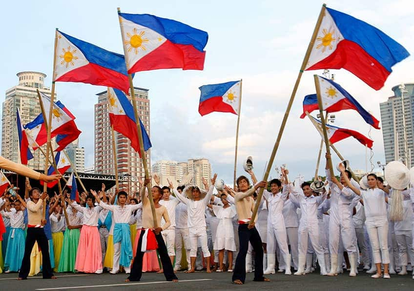 a group of people wave a bunch of Philippine flags