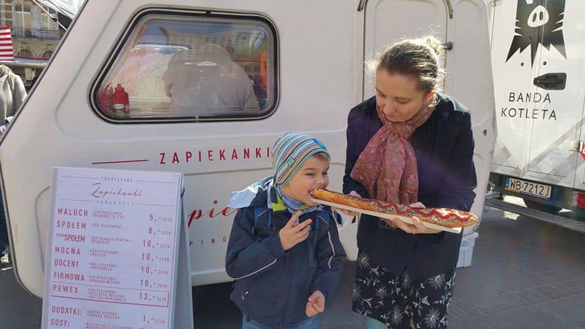 mother and kid buying a pizza from a food truck