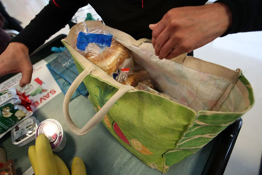 close up of cloth bag being filled with groceries by unseen person at the checkout
