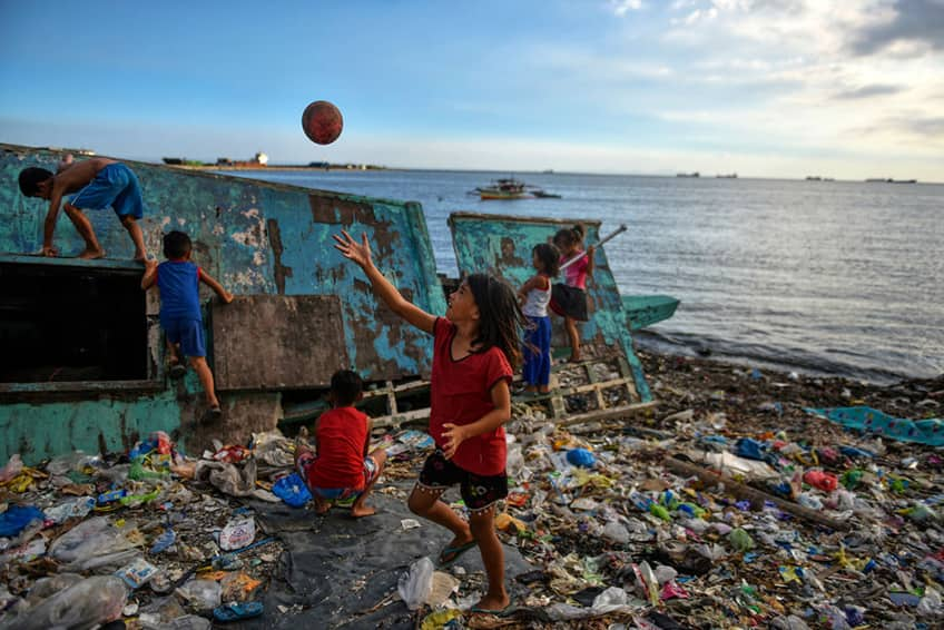 young children playing on a beach completely covered in washed up plastic