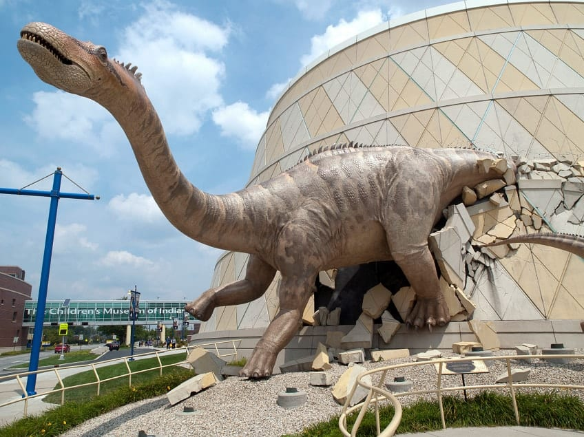 A big dinosaur breaking through one of the museum's walls