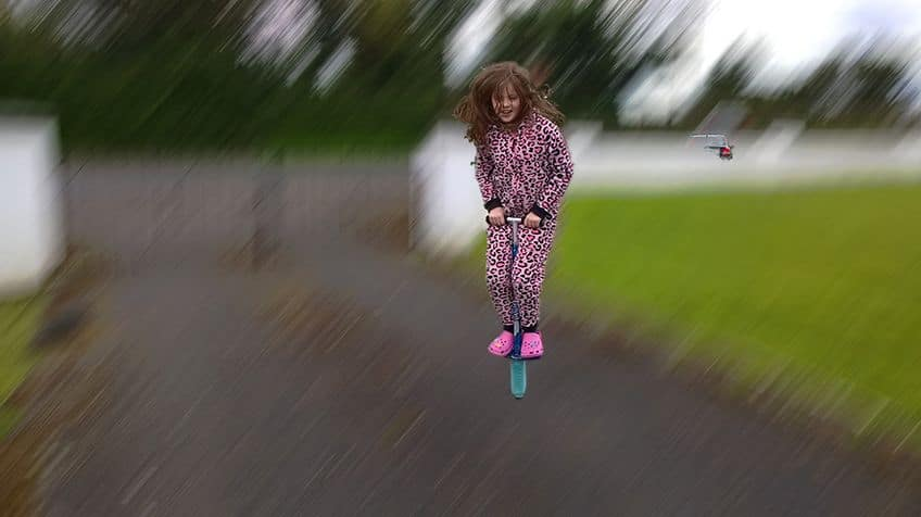 Girl jumps on pogo stick.