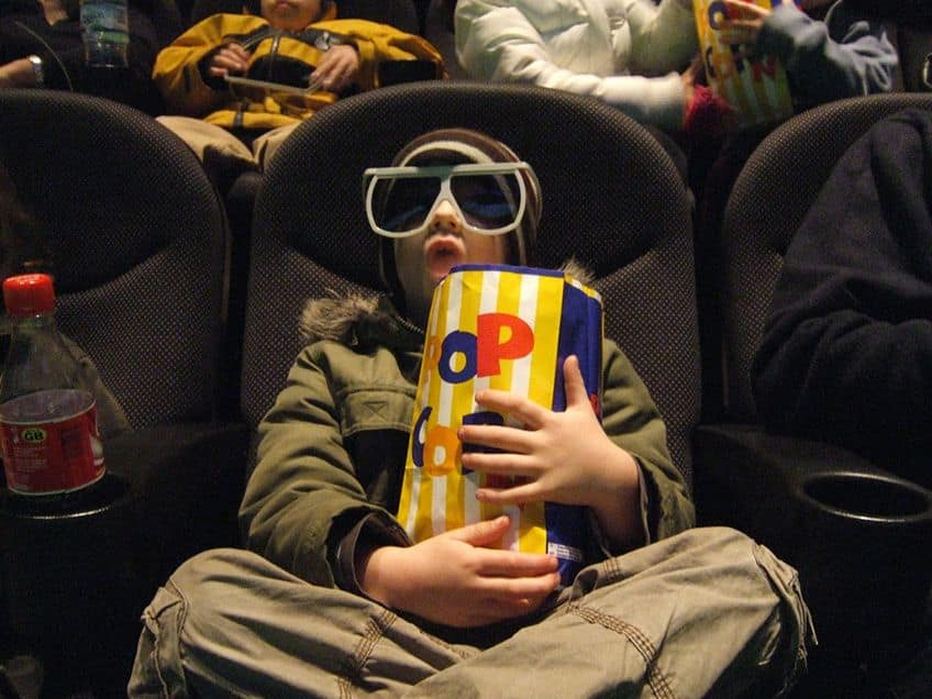 kid in a theatre eating popcorn