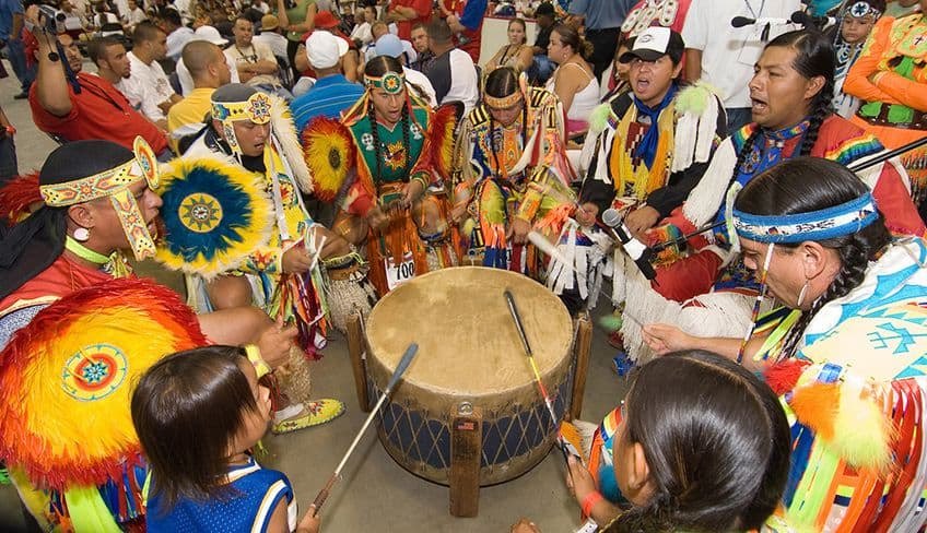 men in regalia in a drum circle