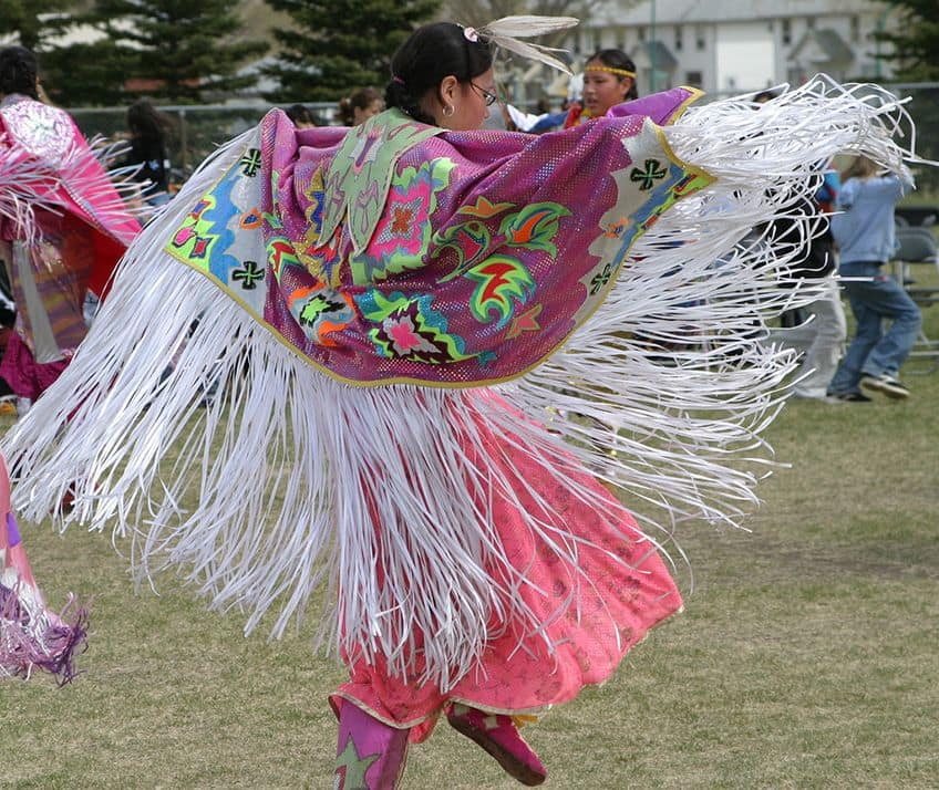 a girl in a pink shawl doing a dance