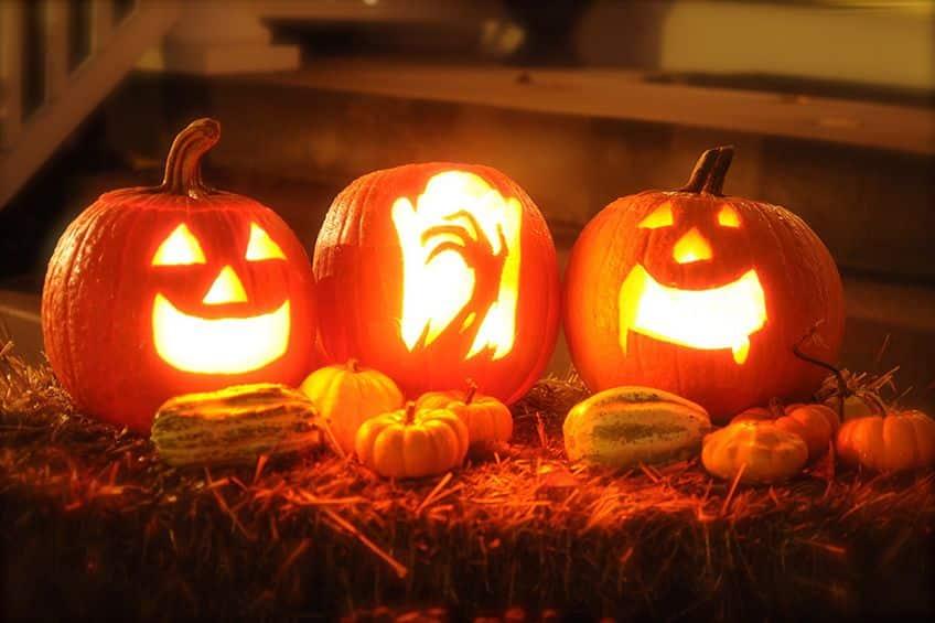 a trio of lit up jack-o-lanterns