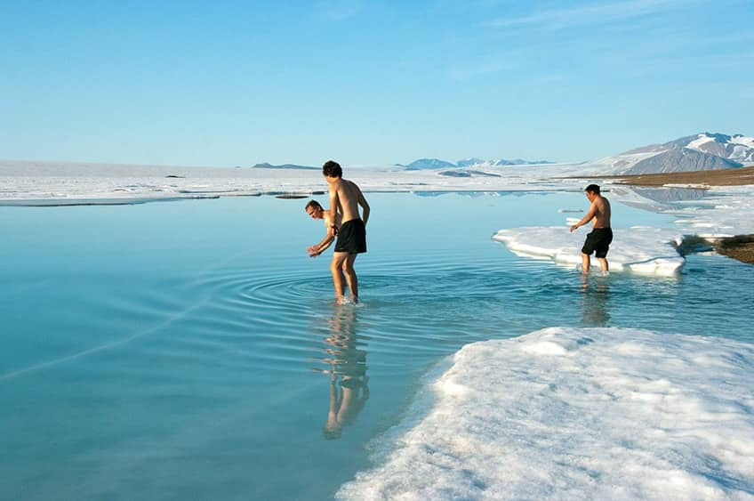three people swimming in the chilly arctic water