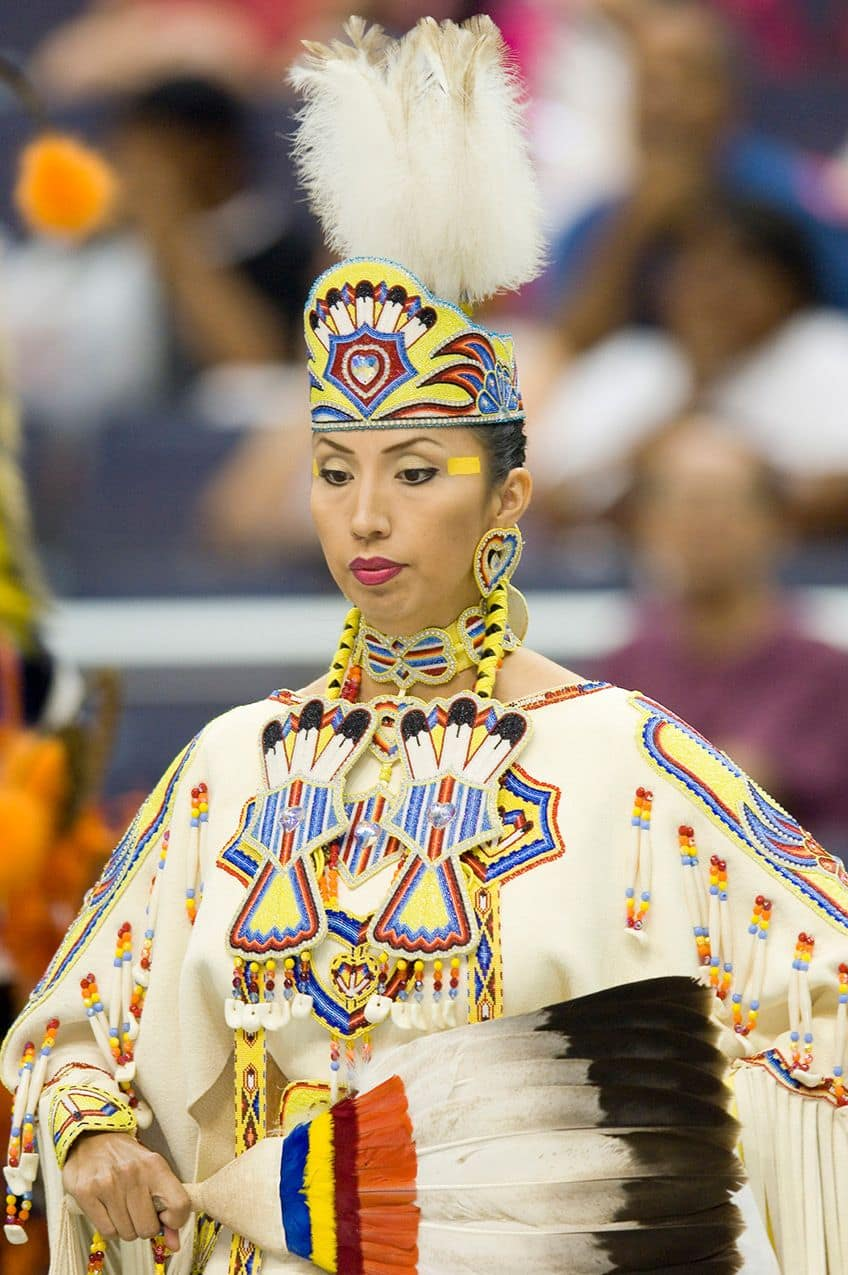 woman wearing a tan buckskin dress covered in beadwork and holding a feather fan