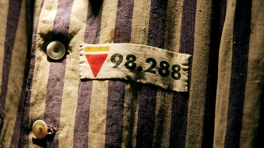 A Holocaust prisoner uniform with the rosa winkel symbol.