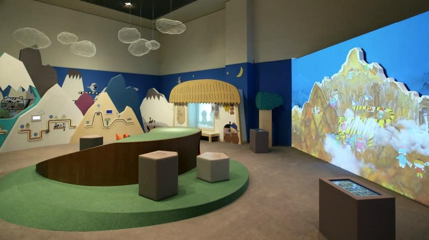 A big screen with a mountain and colourful animals in a room with clouds, fake grass with a hill and even more mountains