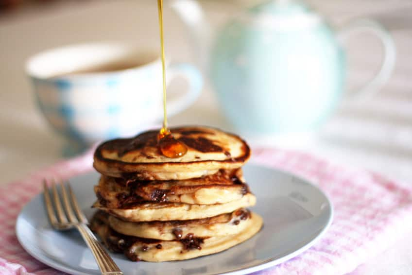 stack of pancakes with syrup being poured on them