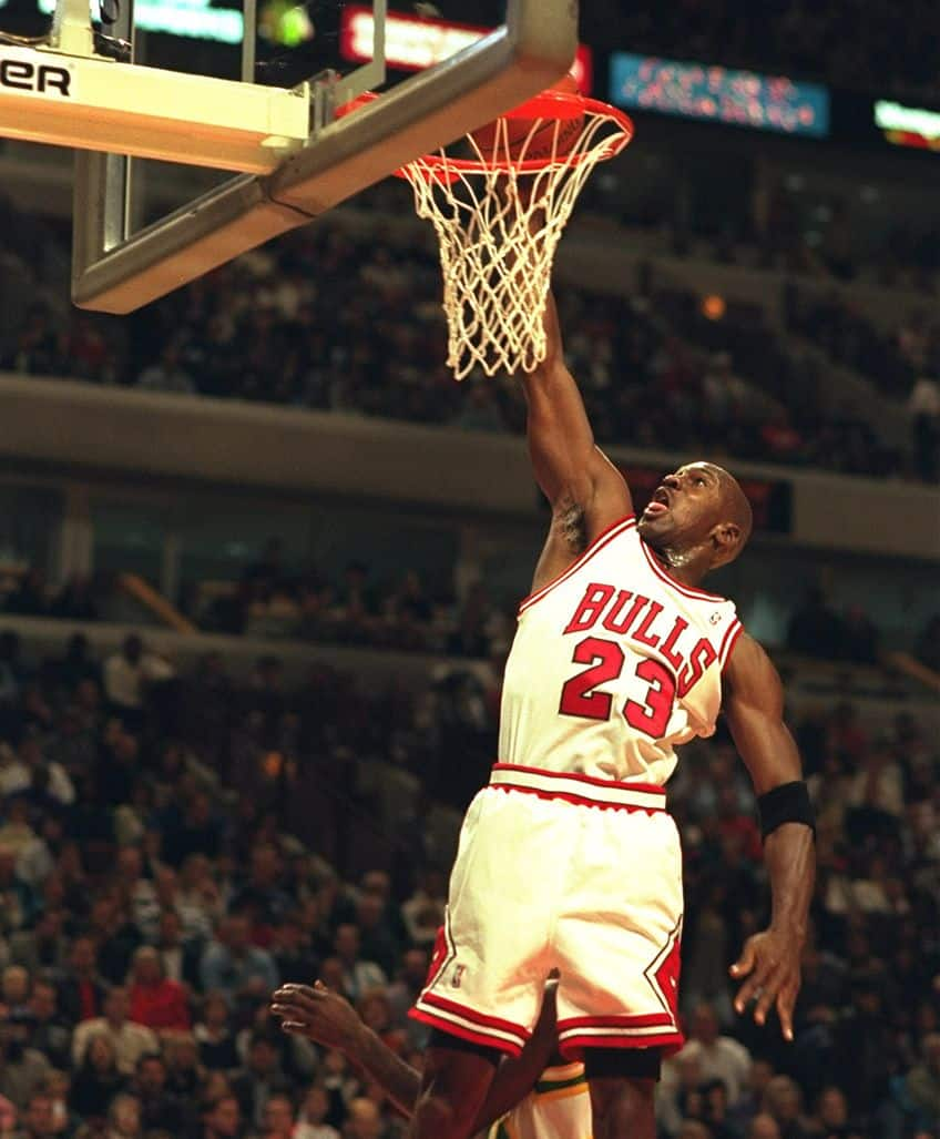 Michael Jordan #23 of the Chicago Bulls does a slam dunk to the joy of the crowd at the United Center in Chicago, Illinois during the game against the Seattle Supersonics.