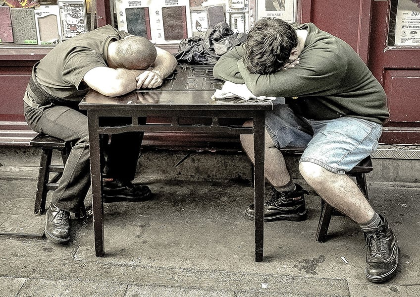 two guys sleeping at a table