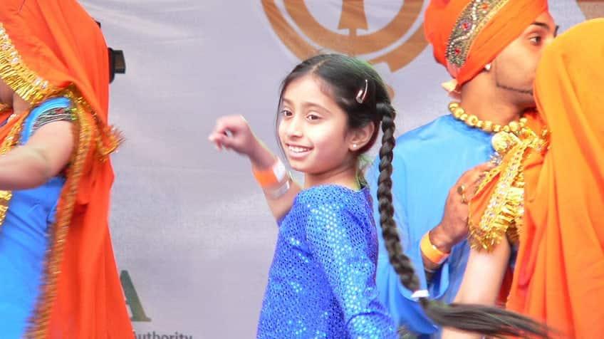 Smiling girl dances the Bhangra to celebrate Vaisakhi.