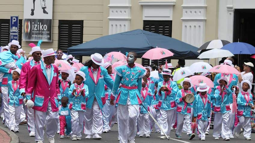 People marching the street all dressed up in pinks and blue suits.