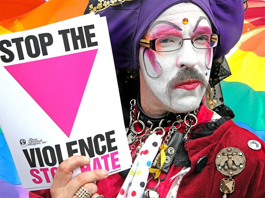 Man dressed as clown holding a Stop the Violence poster.
