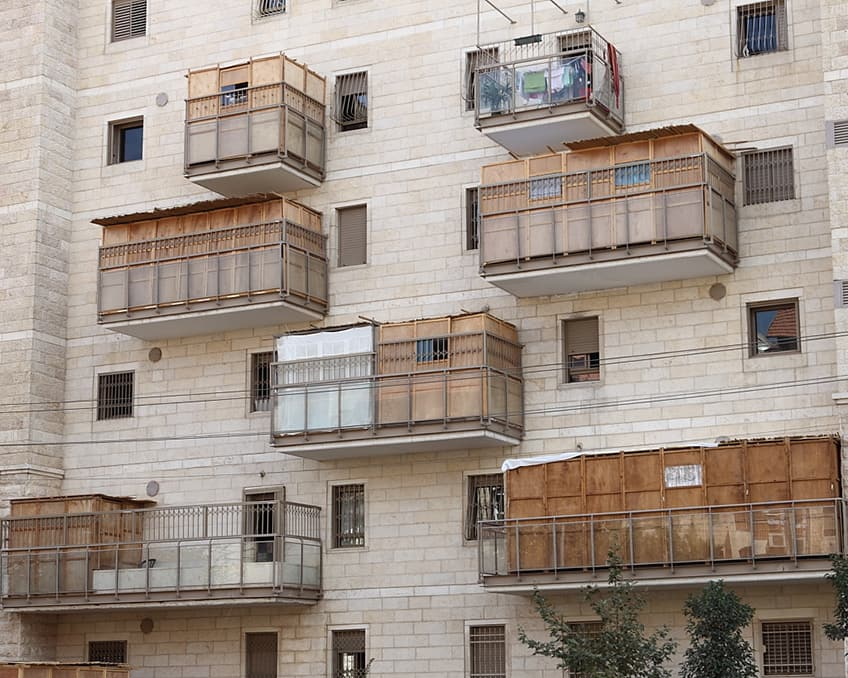 an apartment building with sukkahs on the balconies