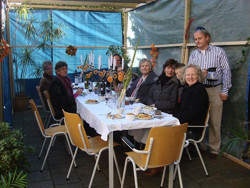 a family sits at the table in their sukkah for dinner