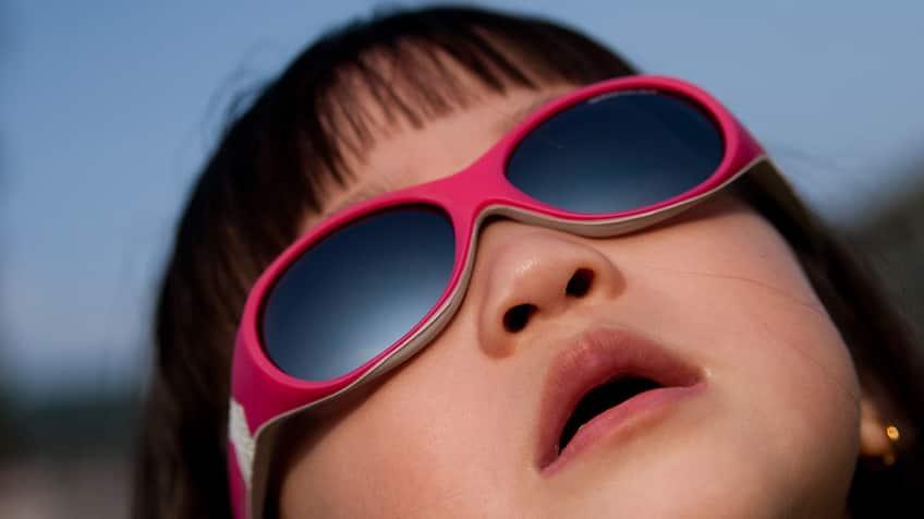 Little girl wearing sunglasses looks up at sun.