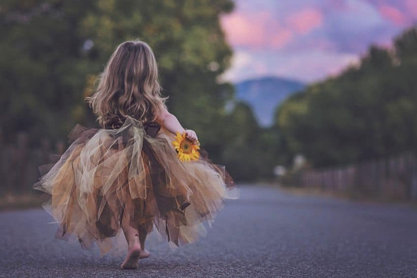 little girl wearing a tutu and walking into a sunset
